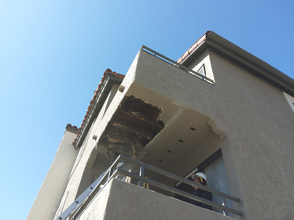 Underside of closed soffit balcony with stucco removed to reveal rotting wood in need of SB721 compliant repairs