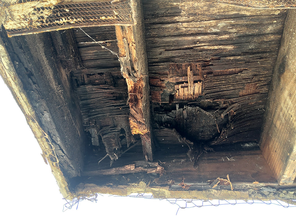 Closeup of underside of balcony requiring SB326 compliant repairs of exterior elevated wood elements