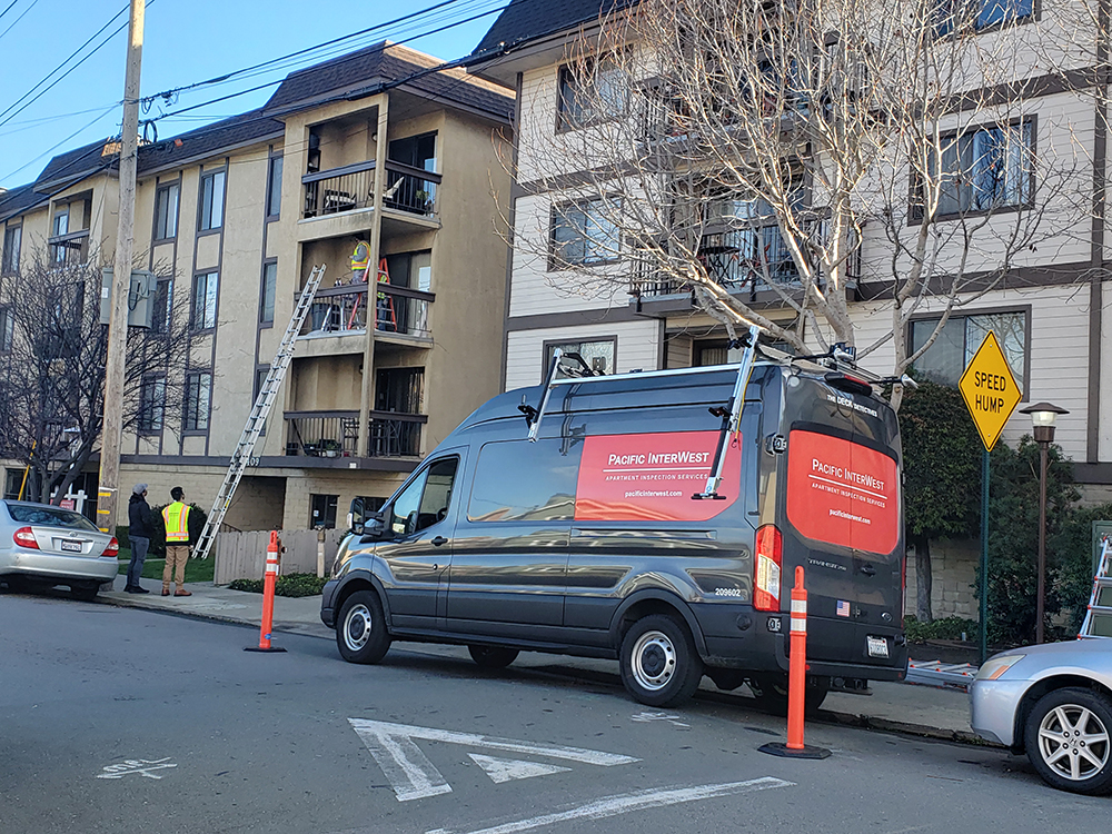 PIW Apartment Inspection Services van parked outside a residential community with inspectors working on nearby balconies