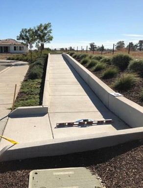 exterior walkway with level and measuring device being inspected for ADA compliance